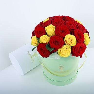 Красные и желтые розы в зеленой коробке