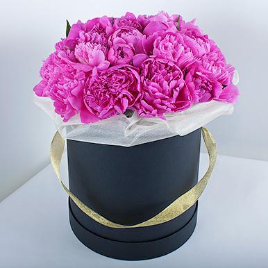 Розовые пионы в черной шляпной коробке
