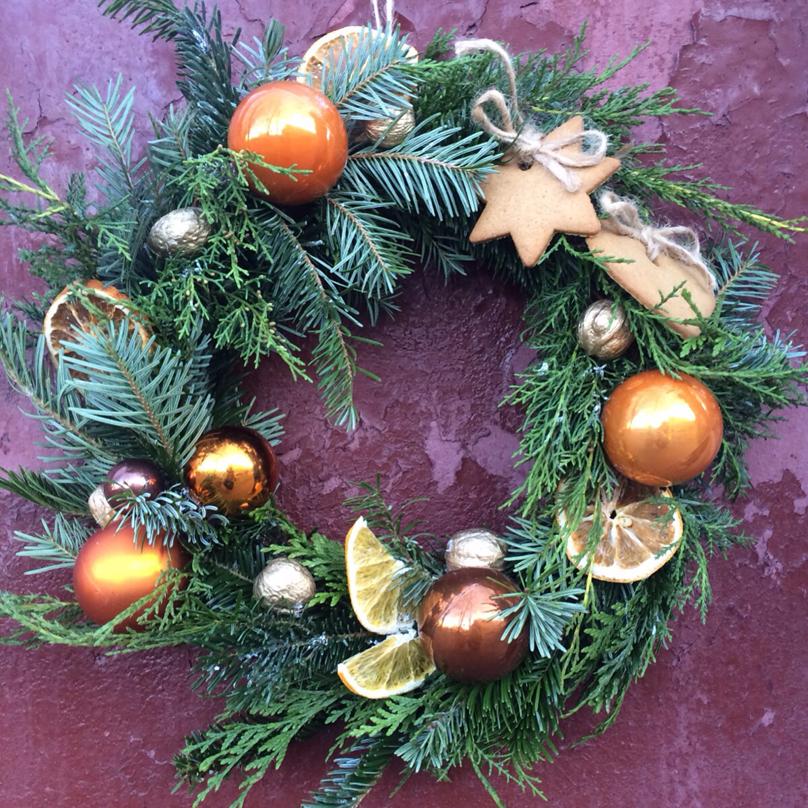 Фото Венок из живой хвои с декором из имбирных пряников, золотых орешков, апельсинов и игрушек