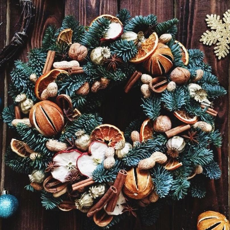 Фото Большой венок из живой хвои с большим количеством декора из натуральных материалов: орехи, яблоки, апельсины, корица, анис