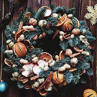 Большой венок из живой хвои с большим количеством декора из натуральных материалов: орехи, яблоки, апельсины, корица, анис